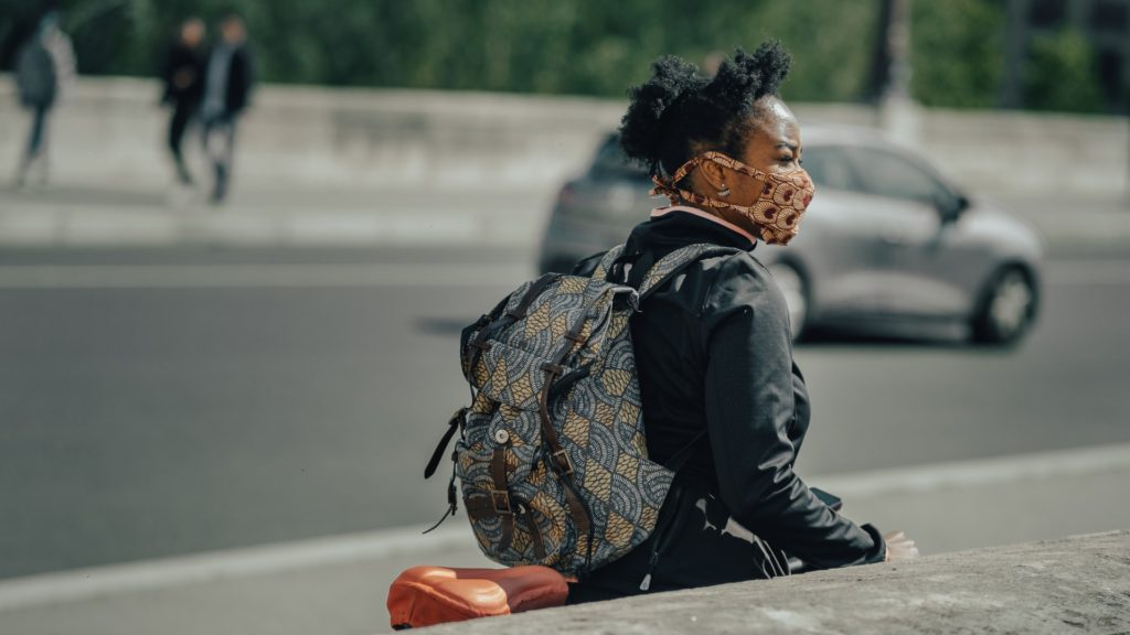 Woman in city, wearing a face mask and backpack.